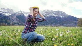 Close up smiling woman in plaid shirt tries dandelion wreath on herself on scenic mountains background. 4k stock video footage