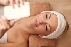 Close up of smiling woman with smartphone in spa Stock Images