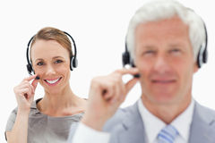 Close-up of a smiling woman talking in background with a white h Royalty Free Stock Photo