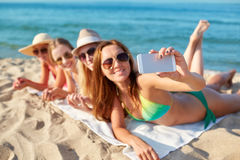 Close up of smiling women with smartphone on beach Royalty Free Stock Photos