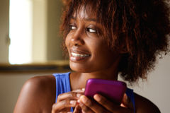 Close up smiling young african woman with cell phone Royalty Free Stock Image