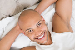 Close up of a smiling young bald man resting in bed Stock Photography
