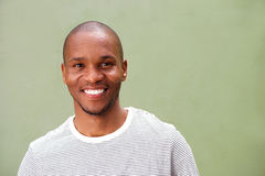 Close up smiling young black man against green background. Close up portrait of smiling young black man against green background Royalty Free Stock Photography