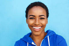 Close up smiling young black woman against blue background Stock Images