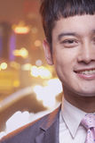 Close-up of smiling young business man, city lights background Royalty Free Stock Photography
