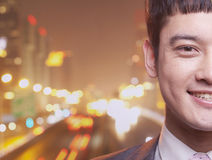 Close-up of smiling young businessman, city lights background Stock Images