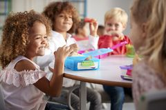Close up of smiling young children sitting at a table eating their packed lunches together at infant school, selective focus stock photography