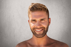 Close up of smiling young man with bristle, trendy hairstyle, pure healthy skin, having glad expression. Attractive macho man smil Royalty Free Stock Image