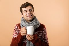 Close up of a smiling young man dressed in sweater. And scarf drinking tea from a cup isolated over beige background stock photos