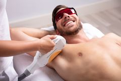Young Man Having Underarm Laser Hair Removal Treatment. Close-up Of Smiling Young Man Having Underarm Laser Hair Removal Treatment In Spa stock photos