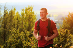 Close up of smiling young man hiking with backpack Royalty Free Stock Photos