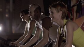 Close-up of smiling young people at fitness center exercising on modern stationary bikes. Slow motion stock video