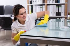 Woman Cleaning The Glass Office Desk With Rag. Close-up Of A Smiling Young Woman Cleaning The Glass Office Desk With Rag In Office royalty free stock photography
