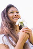 Close-up of a smiling young woman holding flowers Royalty Free Stock Photos