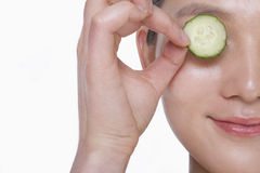 Close up of smiling young woman holding up a cucumber slice over her eye, studio shot Royalty Free Stock Photography