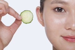 Close up of smiling young woman holding up a cucumber slice, studio shot Royalty Free Stock Image