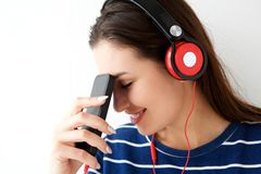 Close up smiling young woman listening to music with mobile phone and headphones. Close up portrait of smiling young woman listening to music with mobile phone Stock Photo
