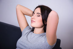 Close up of smiling young woman lying on couch Royalty Free Stock Images