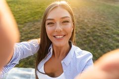 Close up of a smiling young woman taking a selfie royalty free stock photos