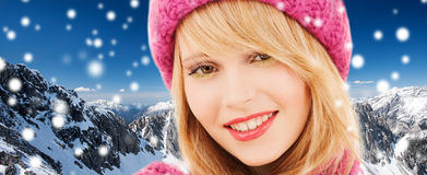 Close up of smiling young woman in winter clothes. Happiness, winter holidays, christmas and people concept - close up of smiling young woman in pink hat and royalty free stock photography