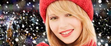 Close up of smiling young woman in winter clothes. Happiness, winter holidays, christmas and people concept - close up of smiling young woman in red hat and royalty free stock photo