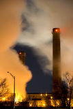 Close-up smoke stacks. Vertical color image of coal fueled power plant with visible smoke stacks and columns of steam Royalty Free Stock Images