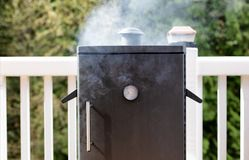 Close up of a smoker with fresh smoke coming out of barbeque coo Stock Images
