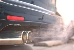 Close up of smoky dual exhaust pipes from a starting diesel car. Close up of smoky dual exhaust pipes from a starting diesel car - emissions scandal royalty free stock photo