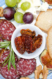 Close-up of snacks - sausage, sun-dried tomatoes, nuts, fruit Stock Images