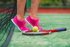 Close up of sneakers near the tennis racquet and Royalty Free Stock Photo