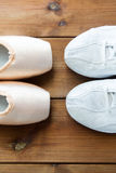 Close up of sneakers and pointe shoes on wood Royalty Free Stock Image