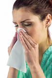 Close-up of sneezing woman with eyes closed and tissue on mouth Royalty Free Stock Photo