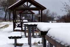 Close up of snow on a brown wooden bench in park Royalty Free Stock Image