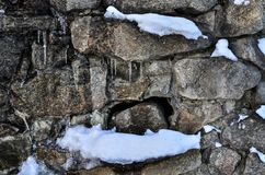 Close-up of a snow-covered icy brick wall with a soft background. stock photos