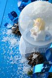 Decorative snow globe with Christmas adornments. Close-up of snow globe with angel inside in composition with Christmas decor on blue snowy surface stock images