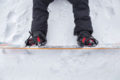 Close up of a snowboard. With bindings and the snowboard boots hooked in.The snowboard is on the snowy ground with a perfect texture stock images