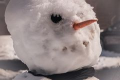 Close-up of snowman face with black eye and carrot. Nose. Black scarf around neck Royalty Free Stock Image