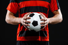 Close up of soccer ball in athlete's hands. Over black background stock photography