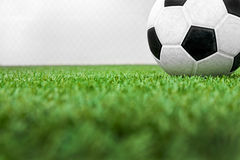 Close up of soccer ball on field. With grass foreground and net background Stock Photos