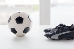Close up of soccer ball and football boots. Sport, soccer, football and sports equipment concept - close up of ball and boots on table Stock Photos