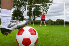 Close up of soccer player aiming ball at frightened goalie Royalty Free Stock Photo
