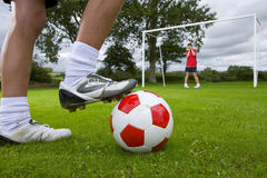 Close up of soccer player aiming ball at frightened goalie Stock Image
