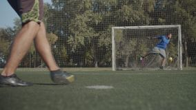 Footballer scoring a goal after penalty shot. Close-up of soccer player legs kicking ball and scoring a goal during penalty shoot-out. Low section of footballers stock footage
