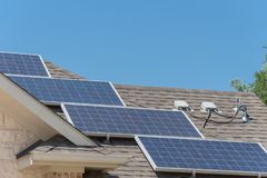 Solar panel system with attic junction box and trees. Close-up solar panel system on asphalt shingles rooftop surround green tree. End run, junction box stock photography
