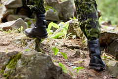 Close up of soldier climbing on rocks in forest Stock Photo
