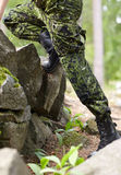 Close up of soldier climbing on rocks in forest Royalty Free Stock Photo