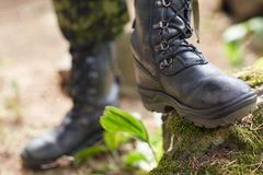 Close up of soldier feet with army boots in forest. War, hiking, army and people concept - close up of soldier feet in army boots in forest Royalty Free Stock Photos