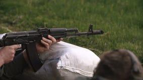 Close-up, soldier firing an AK-47 on the battlefield stock footage