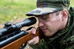 Close up of soldier or hunter with gun in forest Stock Image