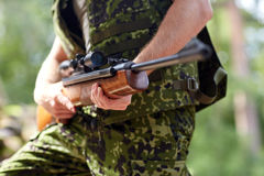 Close up of soldier or hunter with gun in forest Stock Images